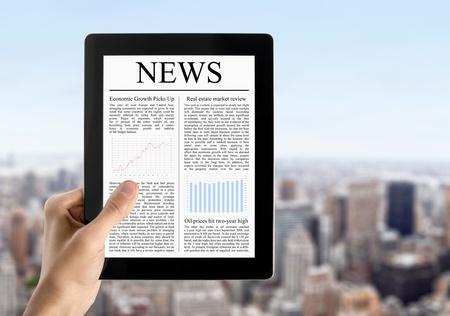 periodicos: Las manos del hombre son el dispositivo de sujeci�n de la pantalla t�ctil con la noticia. Borroso paisaje urbano de rascacielos en el fondo. Foto de archivo