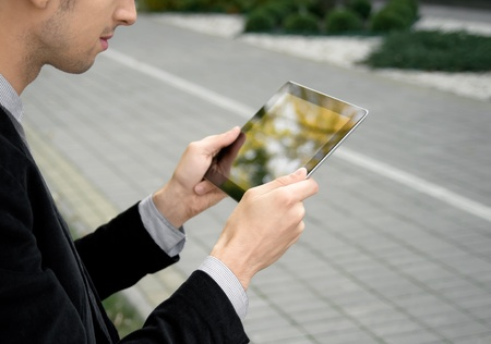 input devices: Businessman working outdoors with tablet pc at the park. Stock Photo