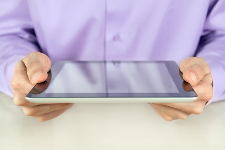 Businessman holding digital tablet pc in hands. Shallow depth of field on fingers. Closeup shot. photo