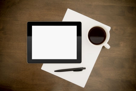 Blank digital tablet with paper, pen and cup of coffee on worktable. Top view.