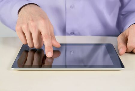 Closeup shot of businessman hands are touching on digital tablet pc. Shallow depth of field on finger. photo