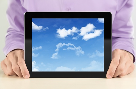 Businessman showing digital tablet pc with cloudscape on screen. Concept image on a cloud-computing theme. photo