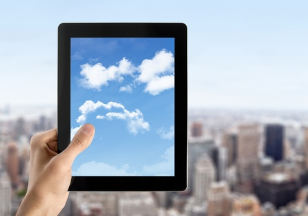 Man hands are holding digital tablet with cloudscape on screen. Concept image on cloud-computing theme. Blurred cityscape with skyscrapers on background. photo