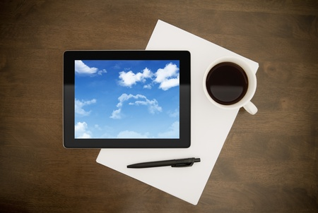 paper screens: Digital tablet with clouds on screen lying on worktable with paper, pen and cup of coffee. Concept image on cloud-computing theme. Stock Photo