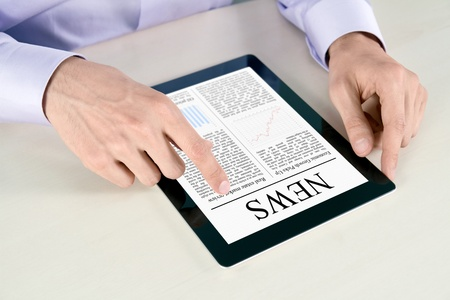 Businessman hands are pointing on contemporary tablet pc with latest news. photo