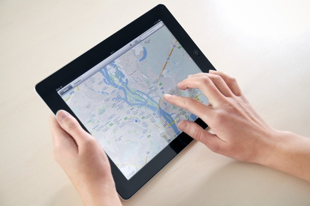Kiev, Ukraine - December 03, 2011: Woman hands holding and touching on Apple iPad2 with Google Maps application on a screen. This second generation Apple iPad2 is designed and development by Apple inc. and launched in march 2011.