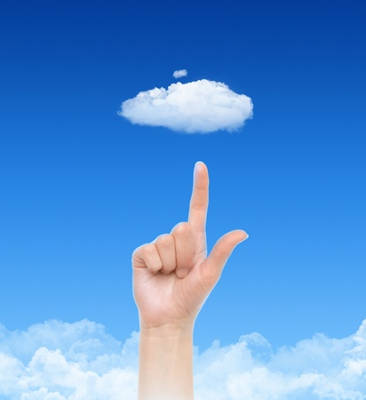 cloud computing concept: Woman hand point on cloud against blue sky with clouds. Concept image on cloud computing and eco theme.