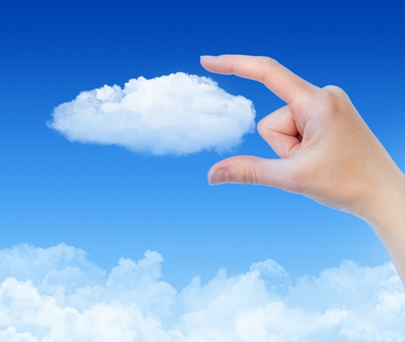 cloud network: Woman hand measures the cloud against blue sky with clouds. Concept image on cloud computing and eco theme. Stock Photo