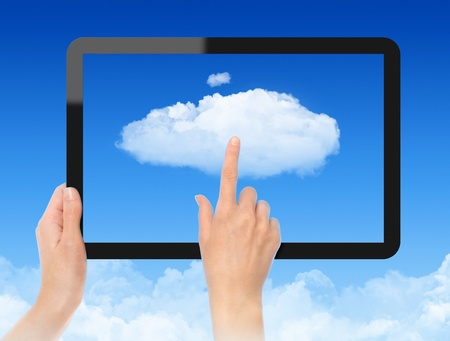 cloud computing concept: Woman hand holding black frame and touch the cloud against blue sky with clouds. Concept image on cloud computing theme.
