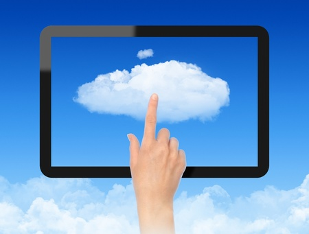 cloud computing concept: Woman hand touch the cloud against blue sky with clouds. Concept image on cloud computing theme.