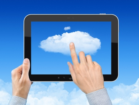 Man hand holding tablet pc and touch the cloud against blue sky with clouds. Concept image on cloud computing theme. photo