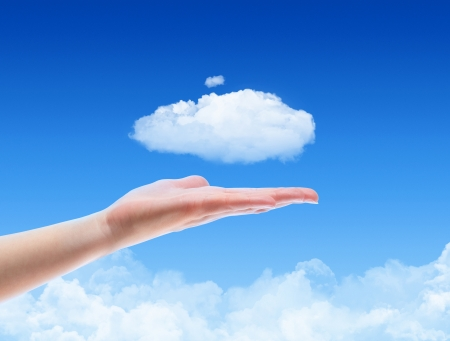 Woman hand offer the cloud against blue sky with clouds. Concept image on cloud computing and ecology theme. photo