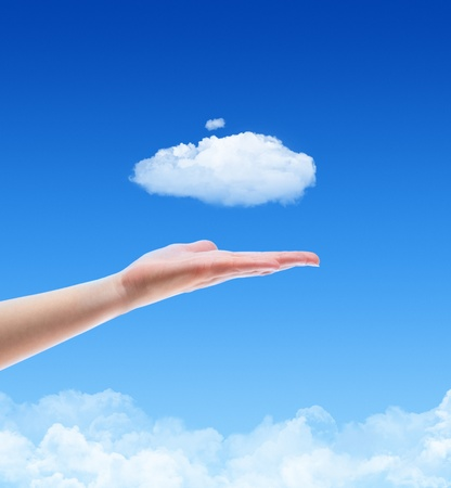 Woman hand offer the cloud against blue sky with clouds. Concept image on cloud computing and ecology theme with copy space. Stock Photo - 12068511