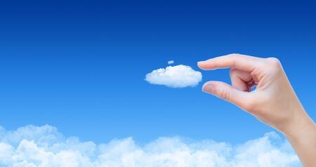 cloud network: Woman hand taking cloud against blue sky with clouds. Concept image on cloud computing and eco theme with copy space.