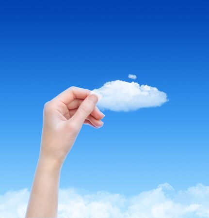 cloud computing: Woman hand hold the cloud against blue sky with clouds. Concept image on cloud computing and eco theme with copy space. Stock Photo