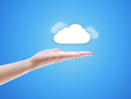 download cloud: Woman hand share the cloud against blue background. Concept image on cloud computing theme with copy space. Stock Photo