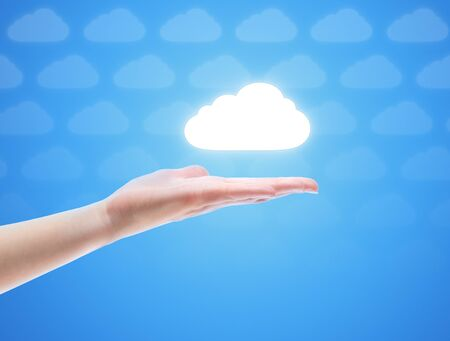 Woman hand share the cloud against blue background with clouds. Concept image on cloud computing theme with copy space. photo