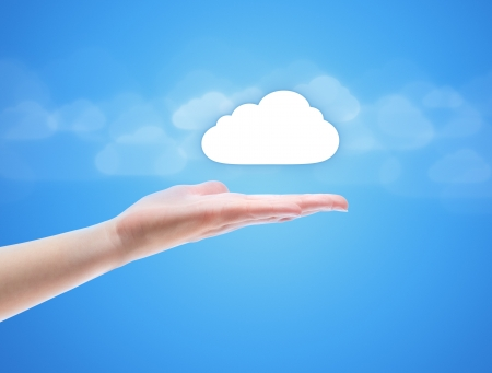 download cloud: Woman hand share the cloud against blue background with clouds. Concept image on cloud computing theme with copy space.