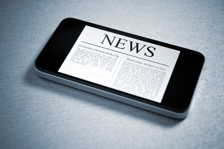 Modern mobile phone lying down on table with fresh news on screen. Added a slight vignetting and toning color for dramatic effect and focus on the main headline. photo