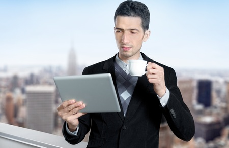 Young businessman with a cup of coffee uses a digital tablet on the roof of business center. Blurred cityscape with skyscrapers on background. Stock Photo - 12181420