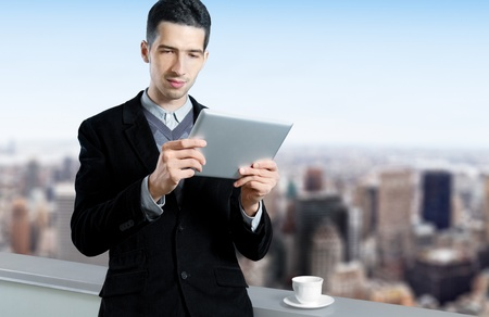 Young businessman with a cup of coffee uses a digital tablet on the roof of business center. Blurred cityscape with skyscrapers on background. Stock Photo - 12181419