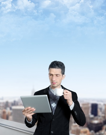 e work: Young businessman with a cup of coffee uses a digital tablet on the roof of business center. Blurred cityscape with skyscrapers on background. Stock Photo