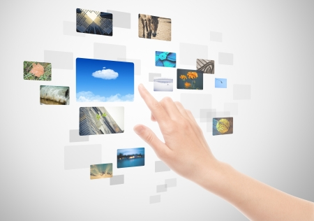 pressing: Woman hand using touch screen interface with pictures in frames. Stock Photo
