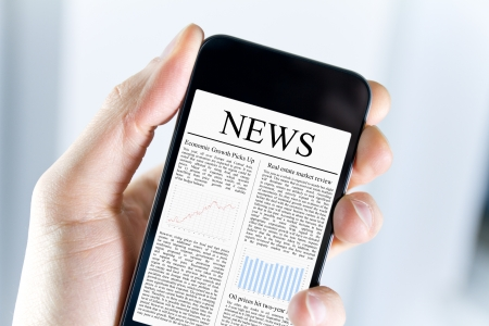 worldwide website: A man holding mobile smart phone with news article on screen. Closeup shot.