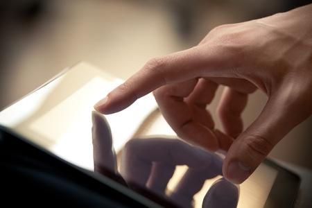 using the computer: Hombre tocando la pantalla a mano en la moderna pc tablet digital plano de la imagen con poca profundidad de campo se centran en el dedo
