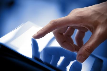 �cran tactile: �cran main de l'homme touchant � un PC moderne tablette num�rique Close-up image avec une faible profondeur de champ accent sur le doigt Banque d'images