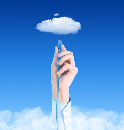 hospedagem: Hand with the cable connected to the cloud. Conceptual image on cloud computing theme.