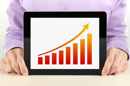 Business man showing tablet pc with success growth graph on screen. Stock Photo - 12750942
