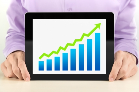 winning stock: Business man showing tablet pc with success growth graph on screen. Stock Photo