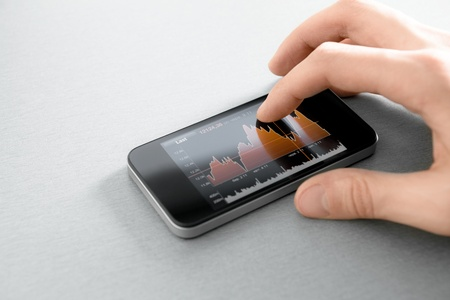 Hand touching stock market chart on mobile smart phone  photo