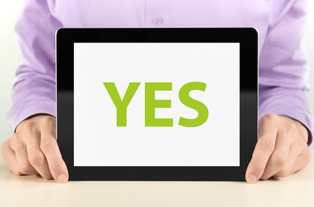 Manager holding tablet pc with  YES  text on screen Stock Photo - 12938528