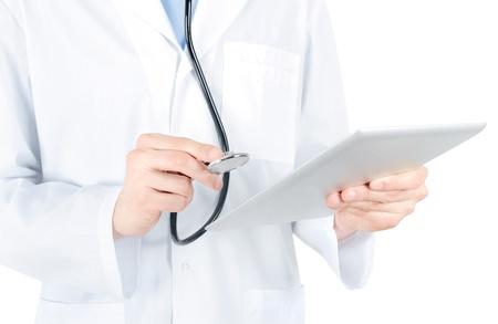 bata blanca: Doctor en bata blanca con el estetoscopio en manos de examen de PC tableta digital aislado en blanco