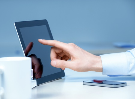 Hand pointing on modern digital tablet pc at the workplace Stock Photo - 13115504