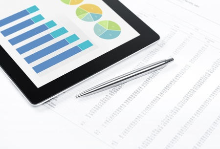analytics: Modern workplace with digital tablet showing charts and diagram on screen, pen and paper with numbers  Stock Photo