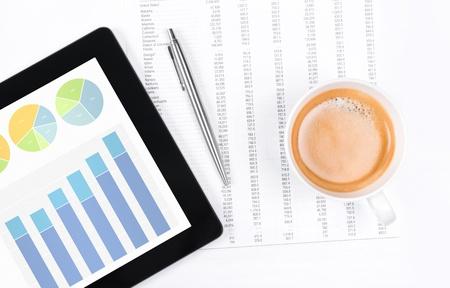desarrollo econ�mico: Lugar de trabajo moderno con la tableta digital que muestra gr�ficos y diagramas en la pantalla, el caf�, l�piz y papel con los n�meros