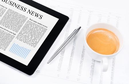 Luogo di lavoro moderno con tavoletta digitale che mostra grafici e diagrammi sullo schermo, carta e penna con i numeri