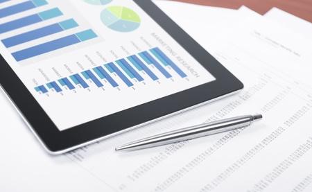 analyse: Lieu de travail moderne avec tablette num�rique montrant des graphiques et des diagrammes � l'�cran, stylo et du papier avec des num�ros