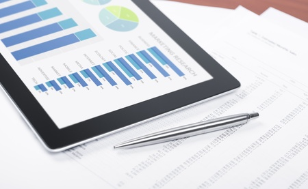 estadisticas: Lugar de trabajo moderno con la tableta digital que muestra gr�ficos y diagramas en la pantalla, l�piz y papel con los n�meros