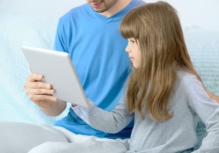 e pretty: Father with daughter using digital tablet for fun  Selective focus on the child