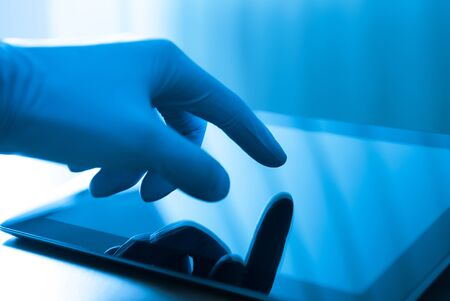 Hand in blue glove touching modern digital tablet Stock Photo - 13545538