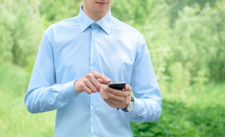 Young businessman using mobile smart phone in the park Stock Photo - 13697493