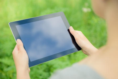 touchpad: Woman using digital tablet PC in the park  Stock Photo