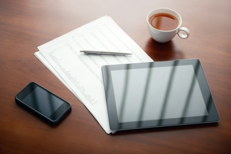 Modern workplace with digital tablet and mobile phone, pen and papers with numbers Stock Photo - 13847724