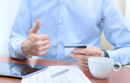 sits: Successful businessman with a credit card in hand, sits at the workplace. Stock Photo