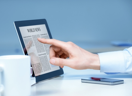 Businessman pointing on modern digital tablet with world news on screen at the workplace Stock Photo - 13952490