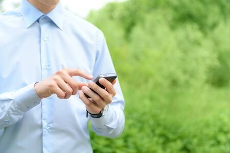 Young man using mobile smart phone in the park  photo